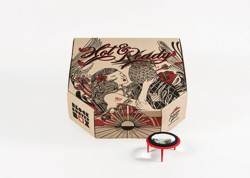 Foto de uma caixa de pizza, feita em papel cartão pardo, com uma ilustração vermelha e preta, de uma menina de cabelos longos e flor vermelha nos cabelos, com uma tatuagem de um abacaxi no braço. A menina esta tentando beijar um homem com cabeça de abacaxi. Grafismos e flores ao fundo da ilustração compõe o design da caixa de pizza. Na frente da caixa, uma lente de aumento envolvida em armação de plástico vermelho e preto, em formato de mesinha, com três pés para apoiarem a lente de aumento como se fosse o centro da mesa.